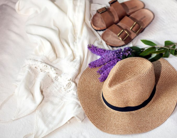 Beach hat, shoes, and lavendar plant on white linens.