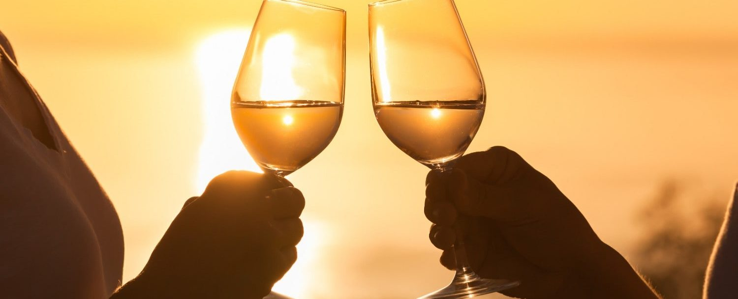 Couple toasting glasses together with sunset in the background.