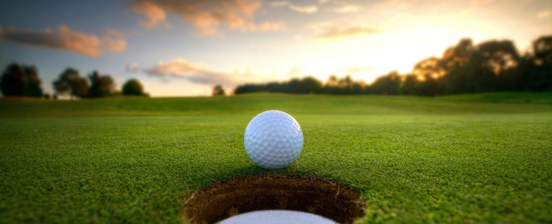 Golf ball near hole at sunset